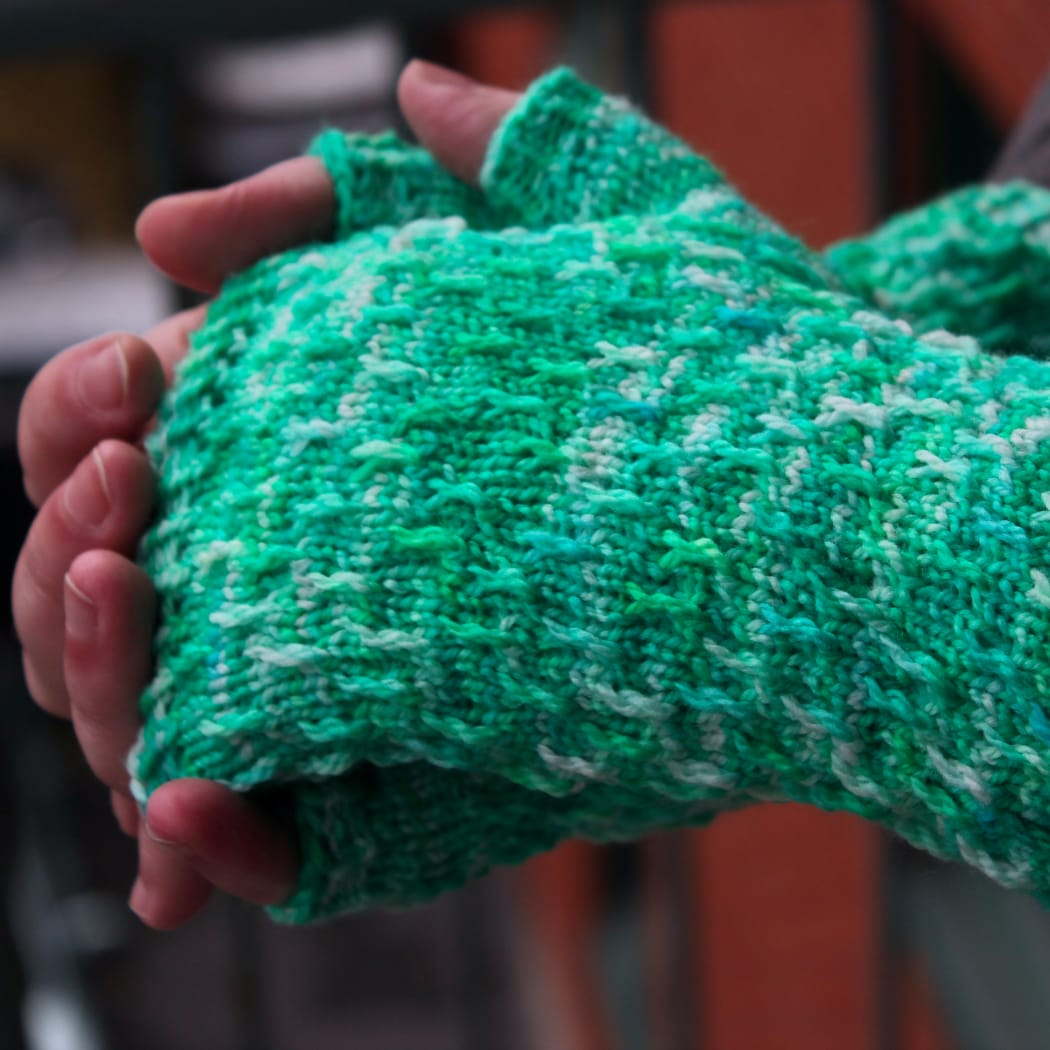 Side view of hands held together wearing bright green, white, and blue fingerless mitts with twisted surface detail.