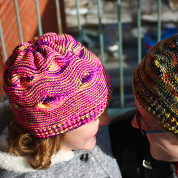 Child wearing yellow, pink, and purple hat with large wavy textured pattern.