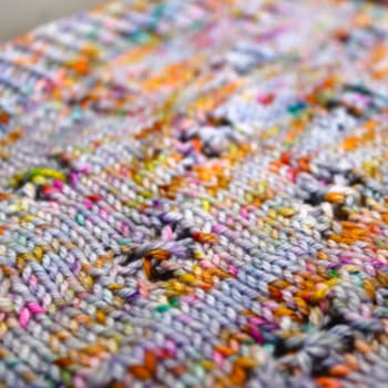 Close up of light purple and rainbow-speckled knitted fabric with lace detail.