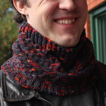 Man wearing cowl that is black with bright orange and burgundy highlights in a zigzag texture.