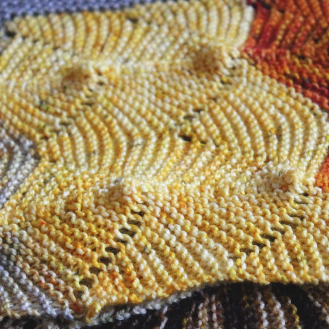 Close up of the edge of a colourful knitted shawl with undulating textured lines.