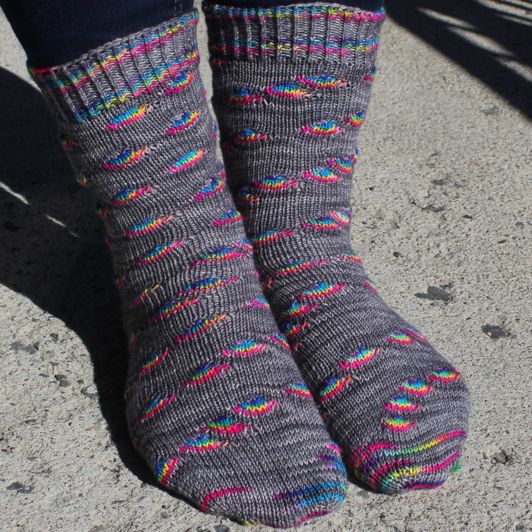 Front view of grey socks with rainbow oval sections and textured cuffs and heels.