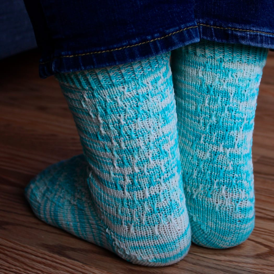 Back view of bright blue and white socks with twisted surface detail.
