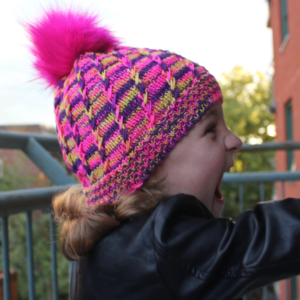 Side view of child wearing bright yellow, pink, and purple toque with pink pompom and spiralling criss-crossing surface texture.