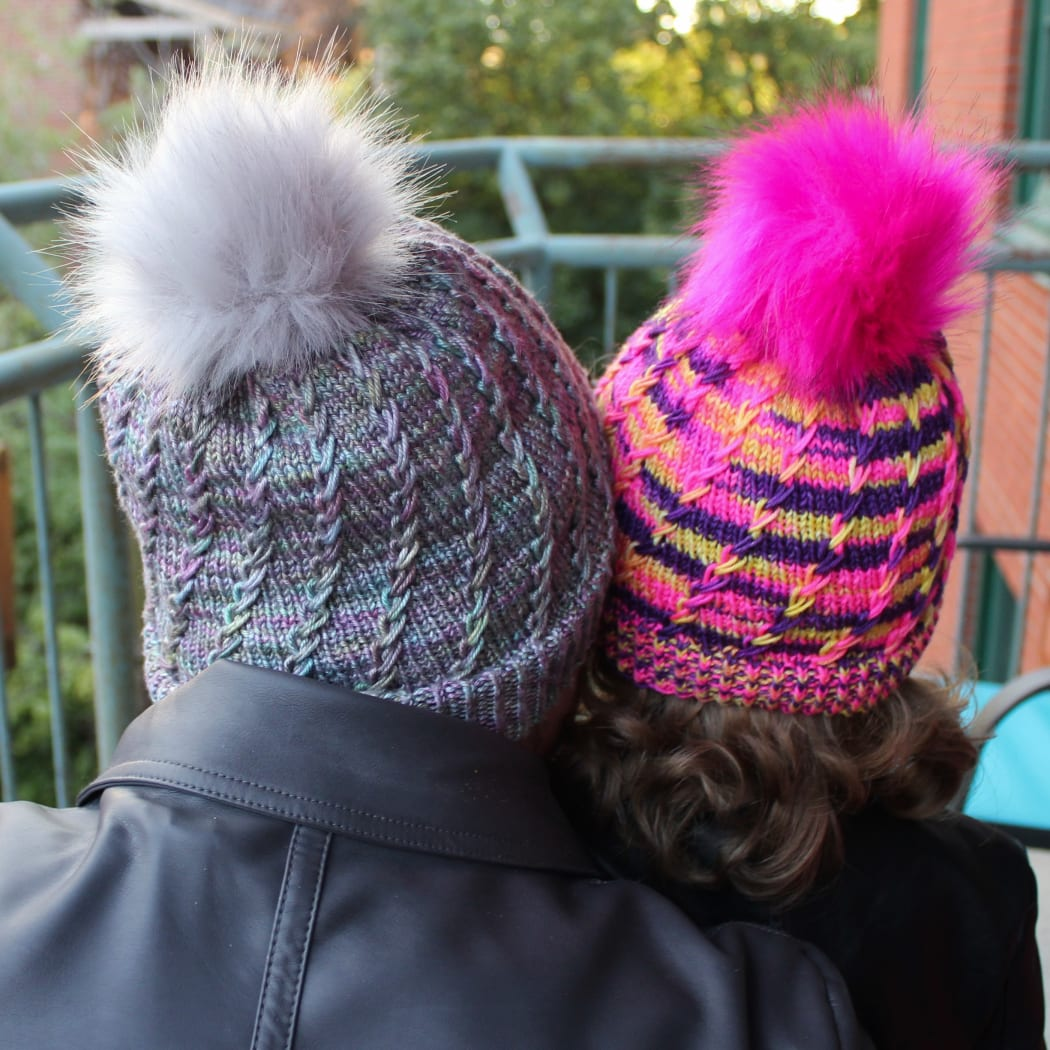 Back view of woman and child wearing toques with spiralling criss-crossing surface textures and coordinating pompoms.