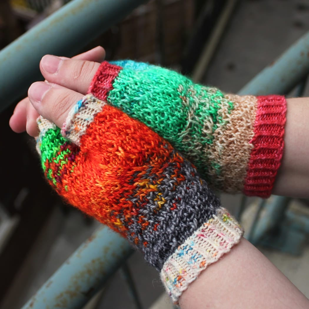 Side view of mismatched multicoloured fingerless mitts with slipped-stitch texture.