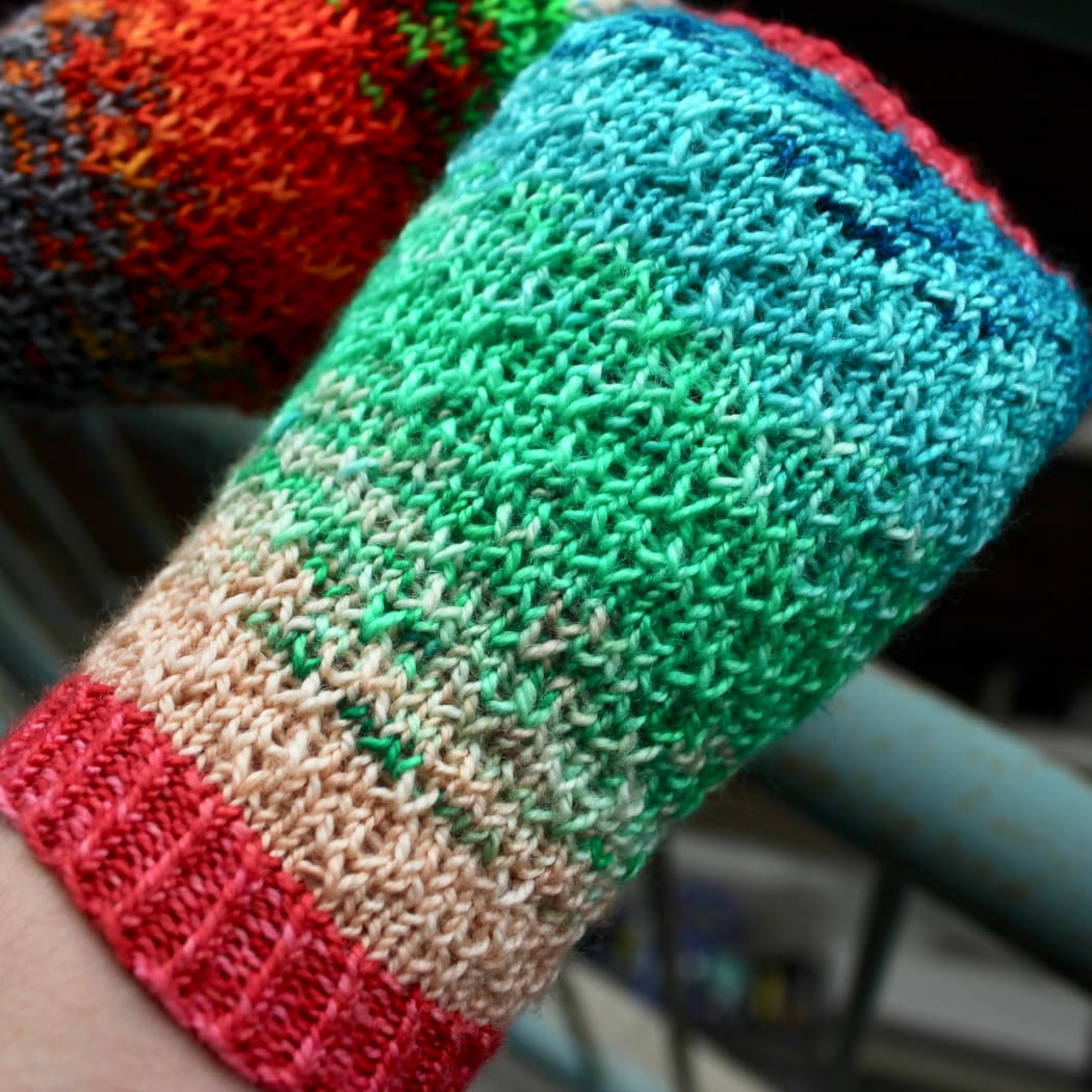 Close-up of mismatched multicoloured fingerless mitts with slipped-stitch texture.