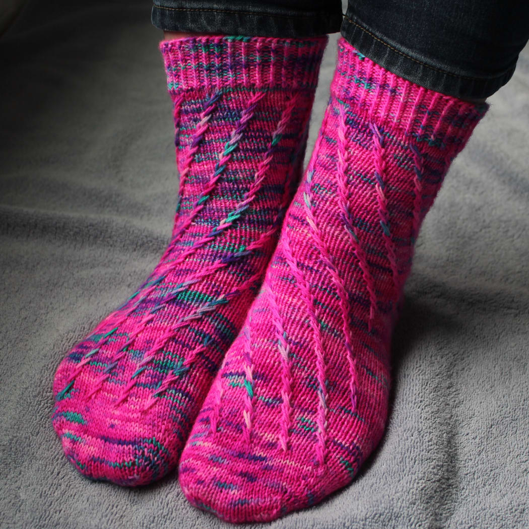 Front view of pink socks with flecks of purple and teal; they have a spiralling criss-crossing surface texture.