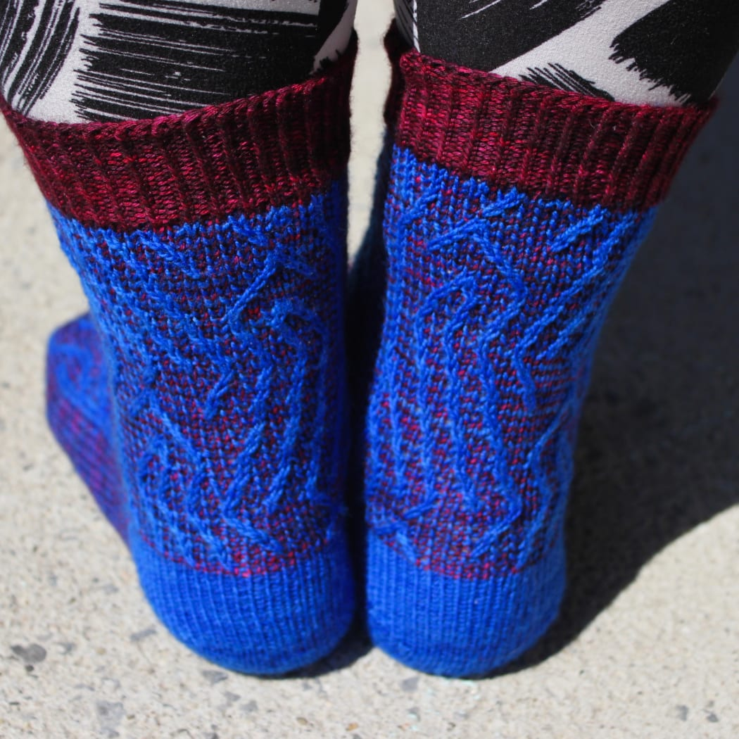 Back view of red and blue socks with vertical stripes that create an abstract surface texture.