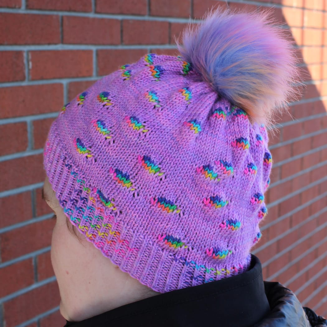 Woman wearing bright purple hat with pompom and randomly-distributed rainbow sections.