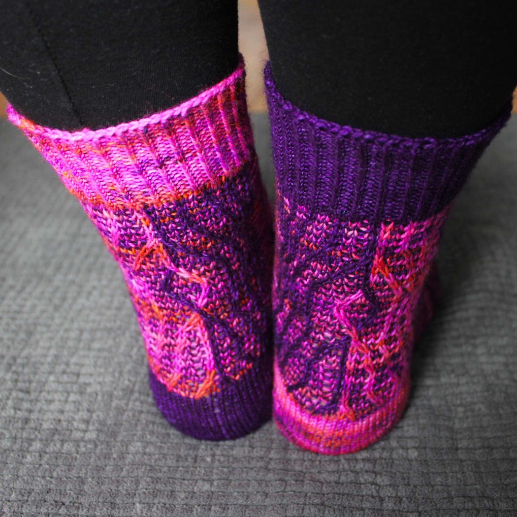 Back view of purple and pink socks with vertical stripes that create an abstract surface texture.