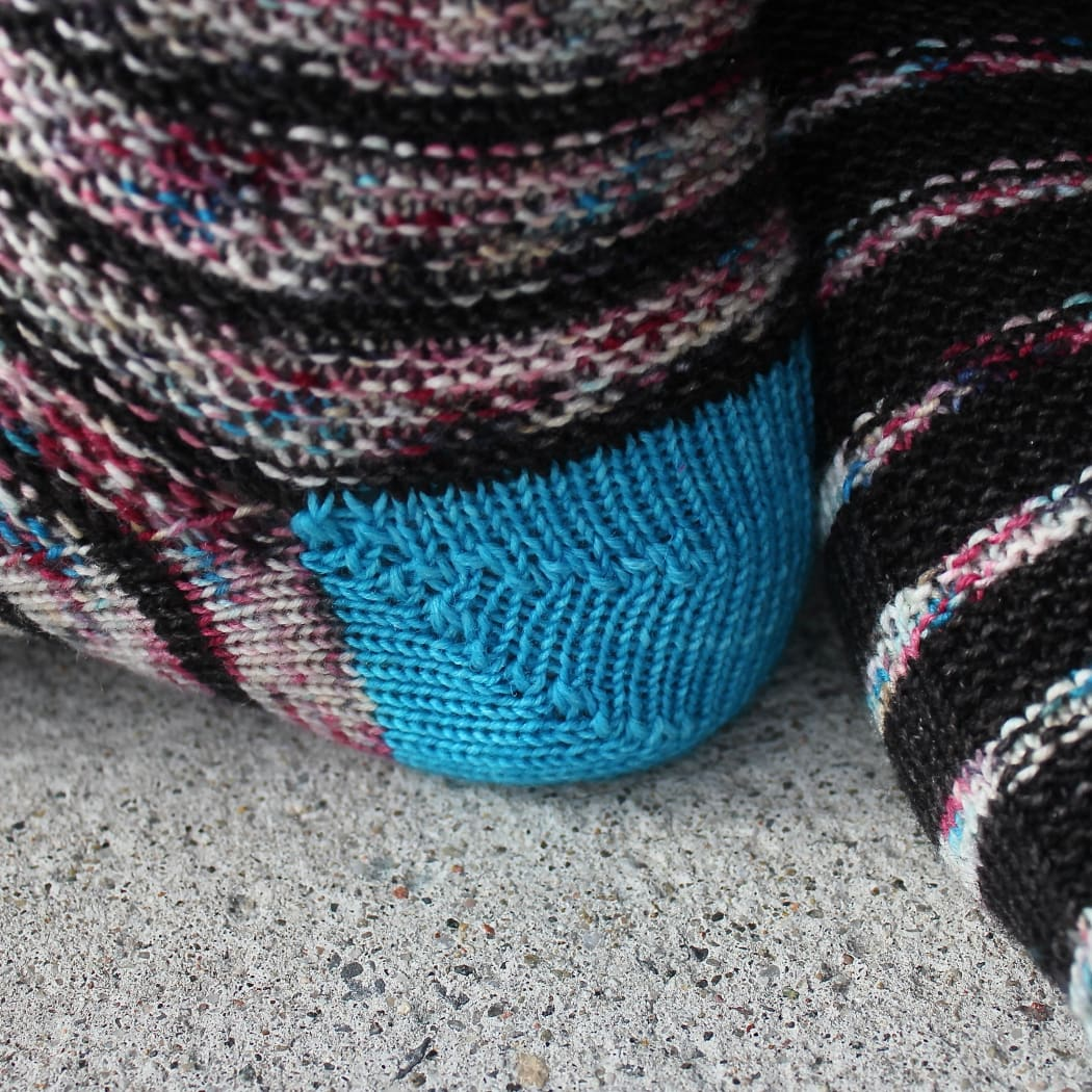 Close-up side view of bright blue rounded three-wedge sock heel.