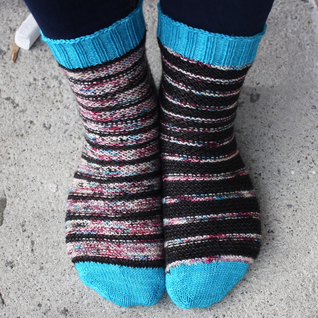 Front view of black and subtly-multicoloured striped socks with bumpy surface texture and bright blue toes and cuffs.