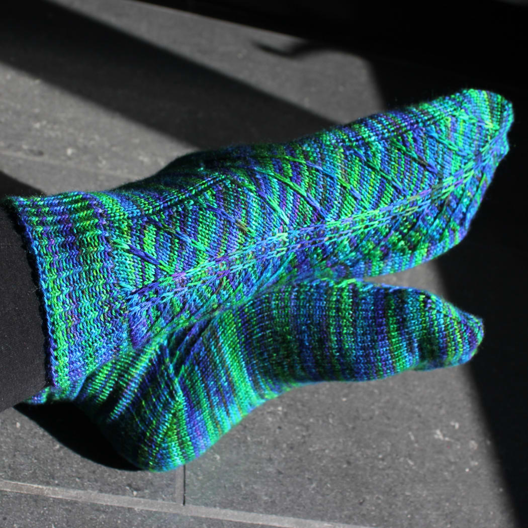 Crossed feet wearing blue-green socks with angled surface detail.