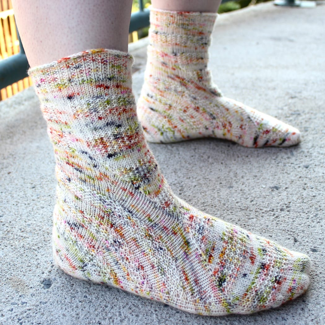 Side view of heavily-speckled white socks with semicircular texture details.