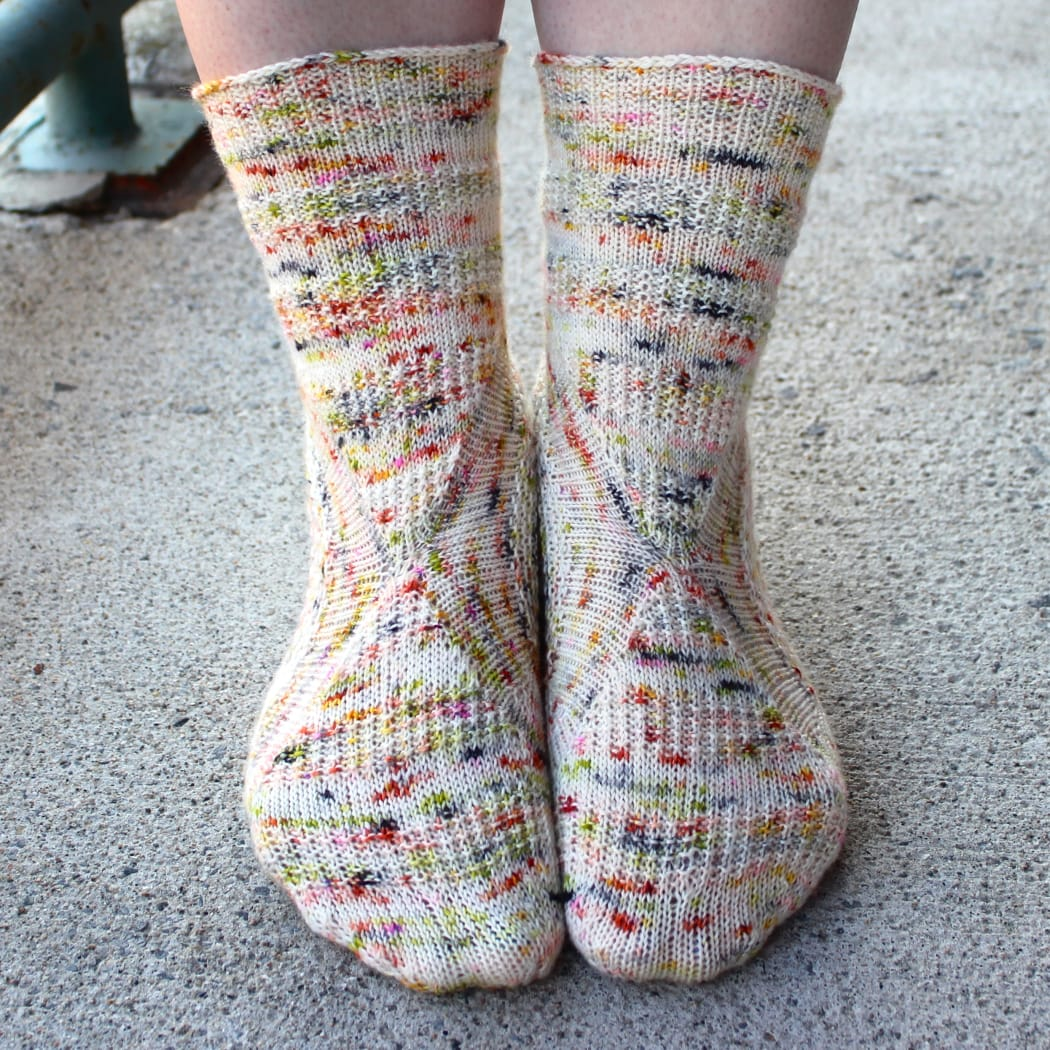 Front view of heavily-speckled white socks with semicircular texture details.