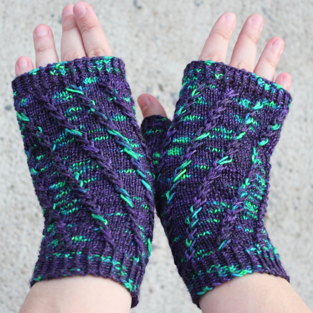 Backs of hands wearing dark purple fingerless mitts with bright green flecks in a twisting spiralling pattern.