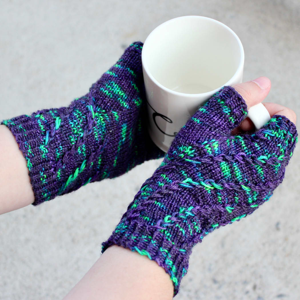 Top-down view of hands holding a white mug and wearing dark purple fingerless mitts with bright green flecks in a twisting spiralling pattern.