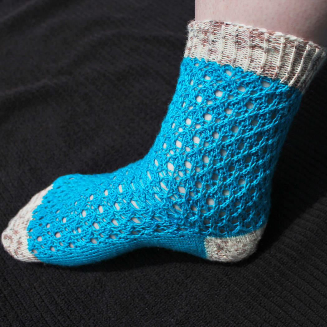 Side view of bright blue lace sock with white and brown speckled heel, toe, and cuff.