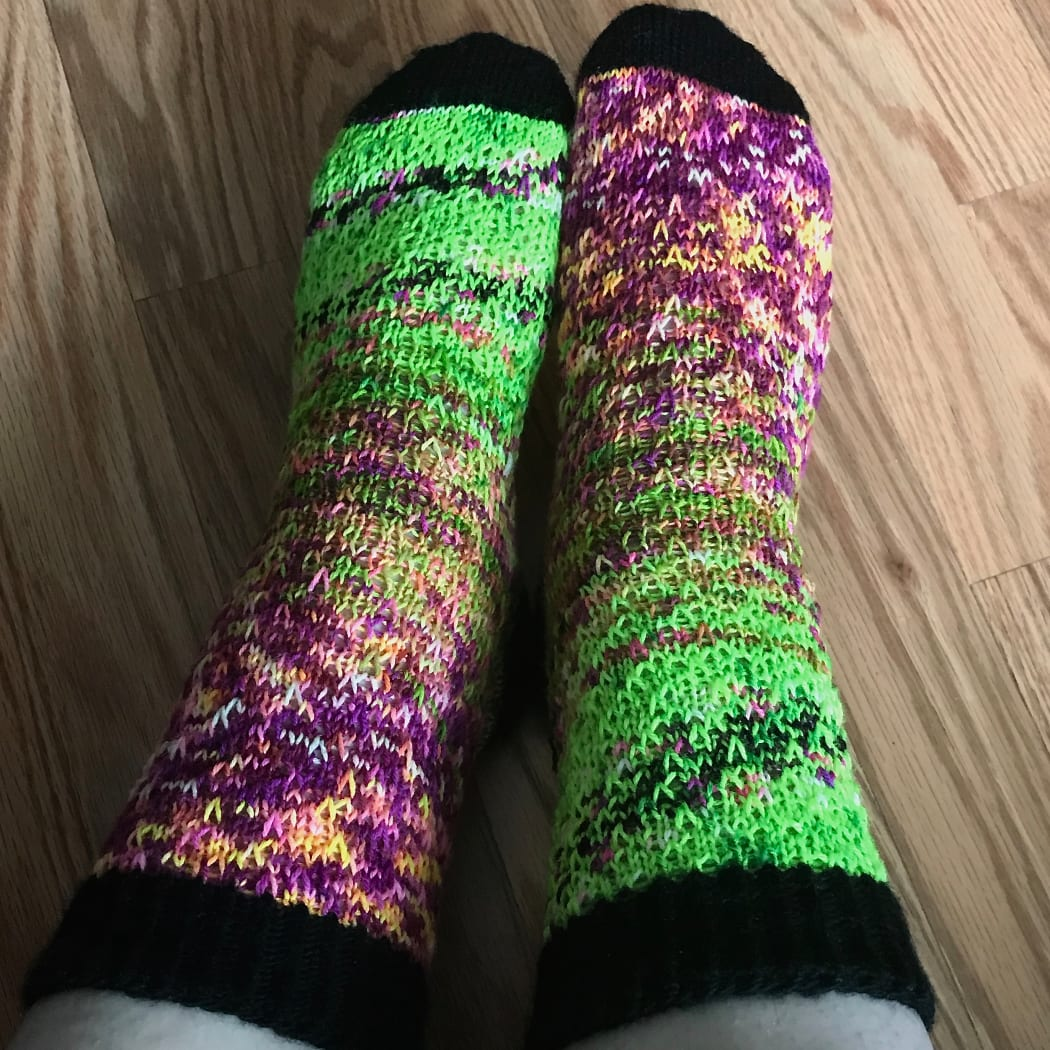 Top-down view of feet wearing green and purple socks with a fade effect with black heels, toes, and cuffs.