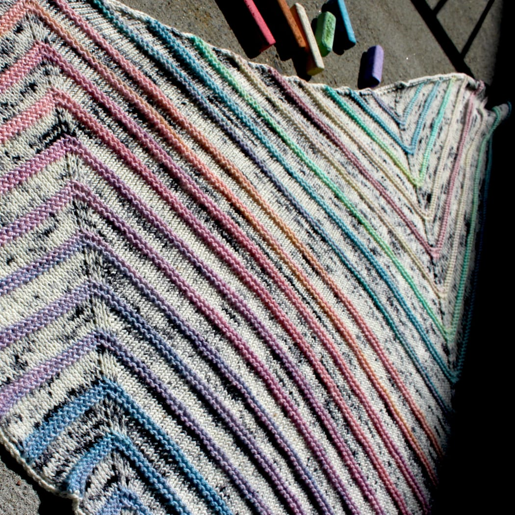 Close-up of a triangular shawl with flat white and black speckled sections between bumpy pastel stripes.