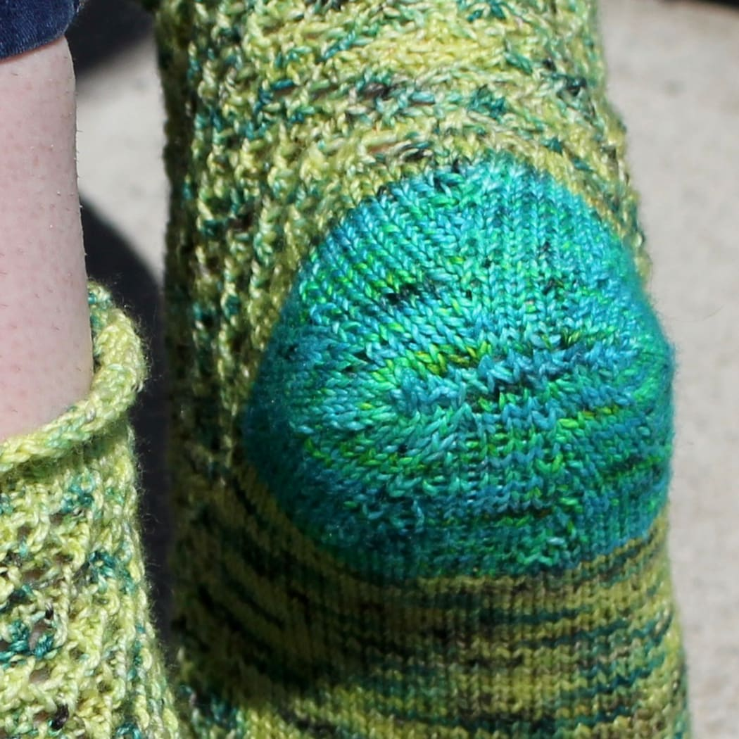 Close up view of bright blue heel on a yellow and green lace sock.