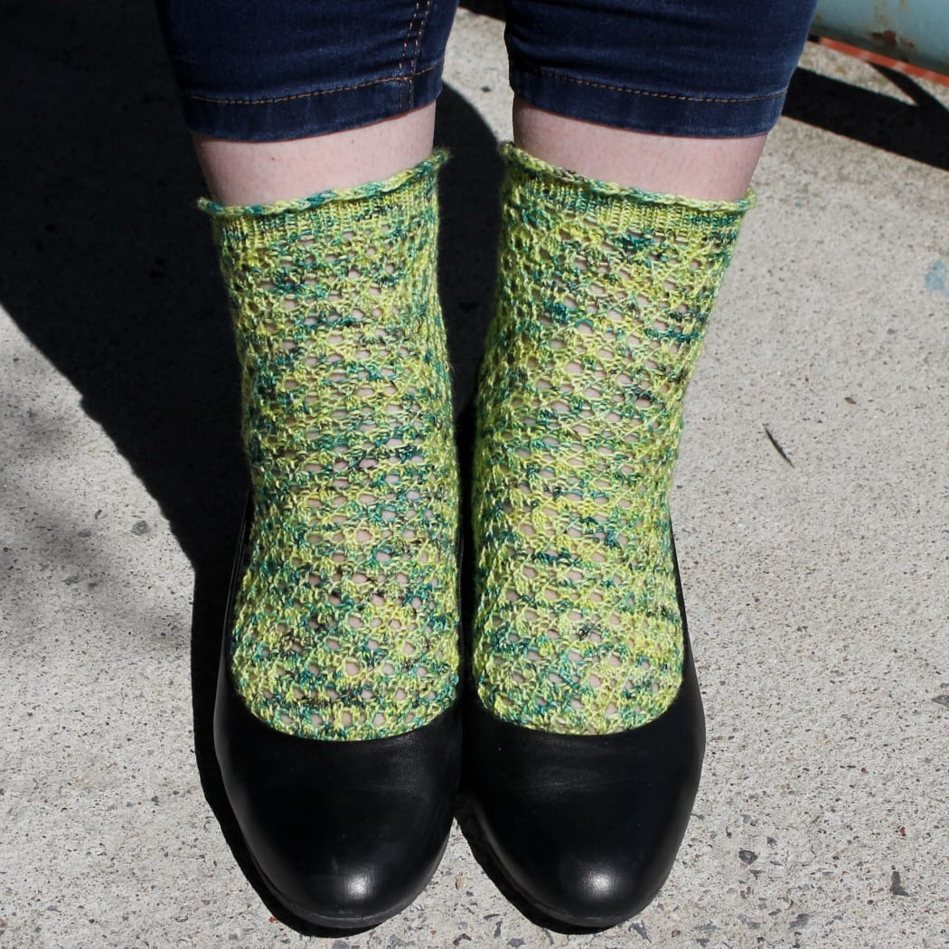 Front view of feet wearing black shoes and yellow and green lace socks.