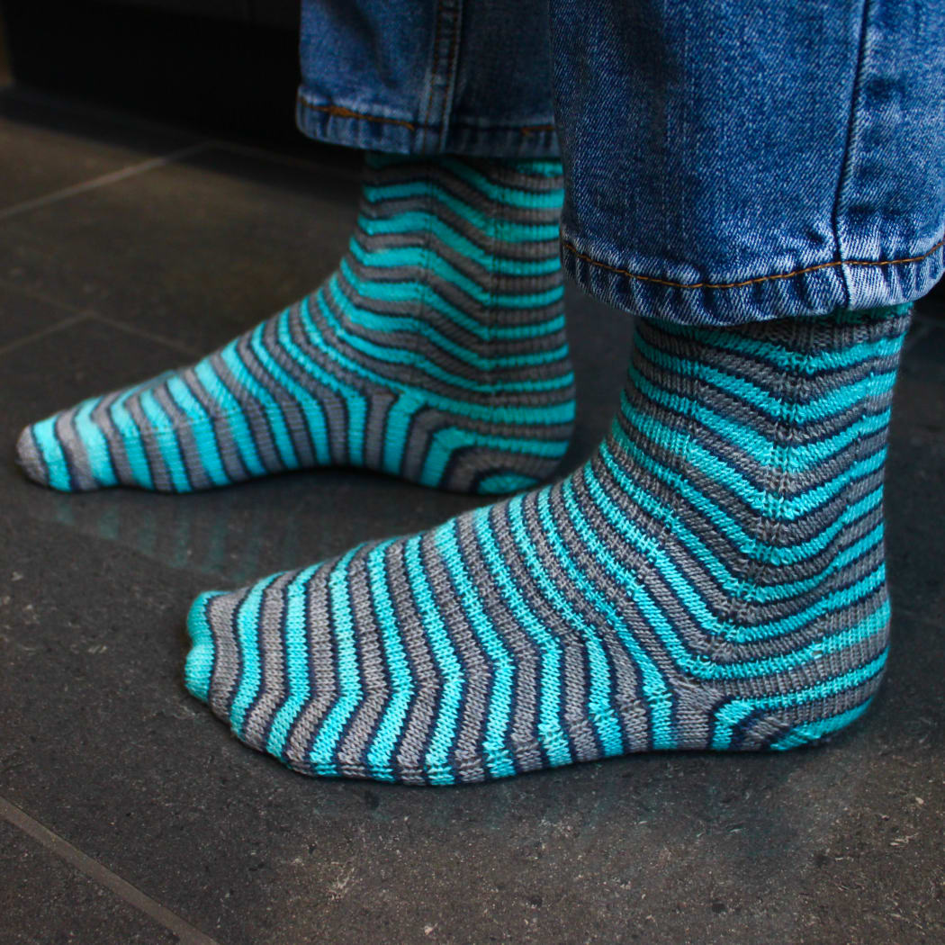 Left-side view of grey and blue socks with stripes that are distorted on the sides.