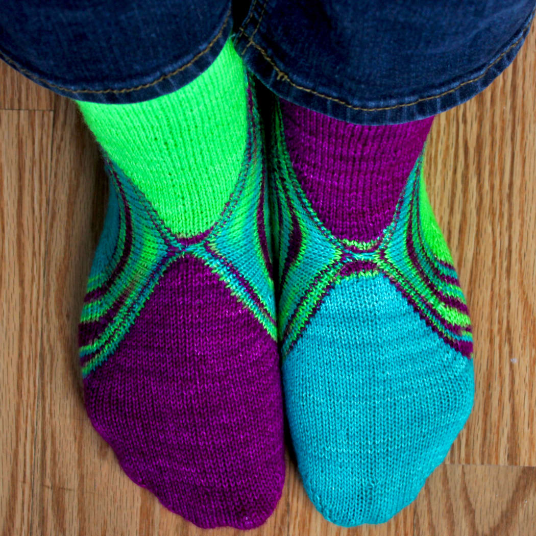 Top-down view of feet wearing bright green, blue, and purple socks with a multicoloured stripe between the colours.