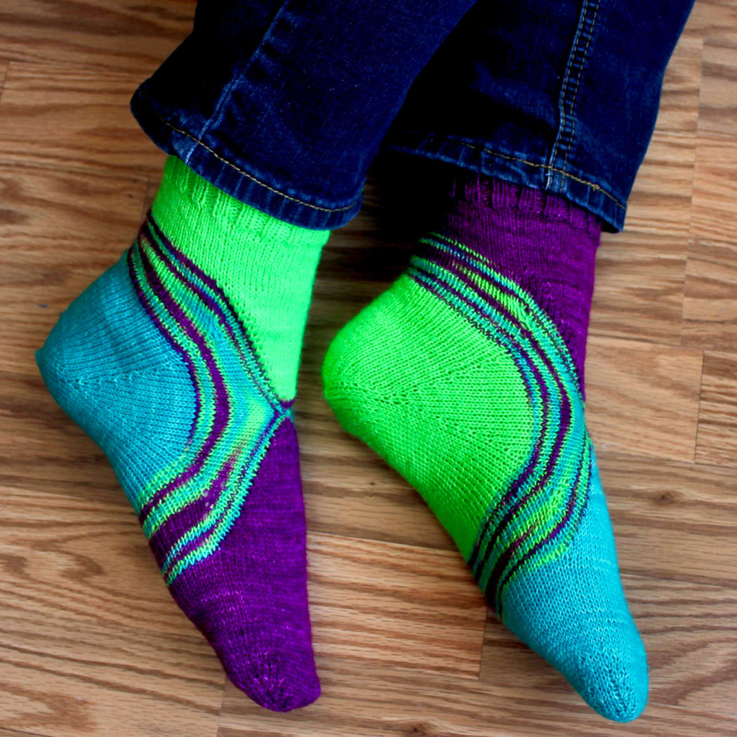 Side view of feet wearing bright green, blue, and purple socks with a multicoloured stripe between the colours.