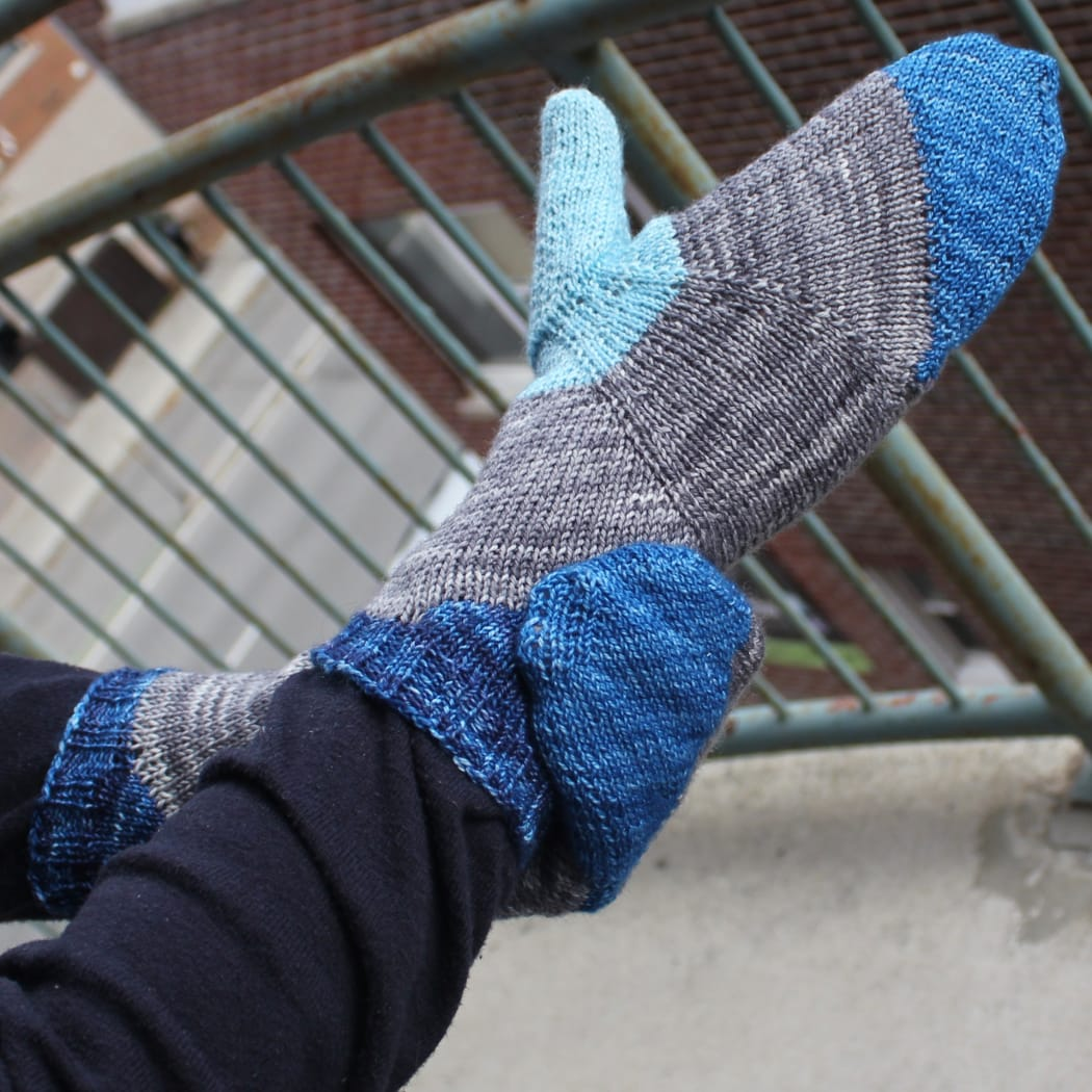 Side view of hand wearing bright yellow, blue, and orange mittens with a multicoloured stripe across the palm between the colours.