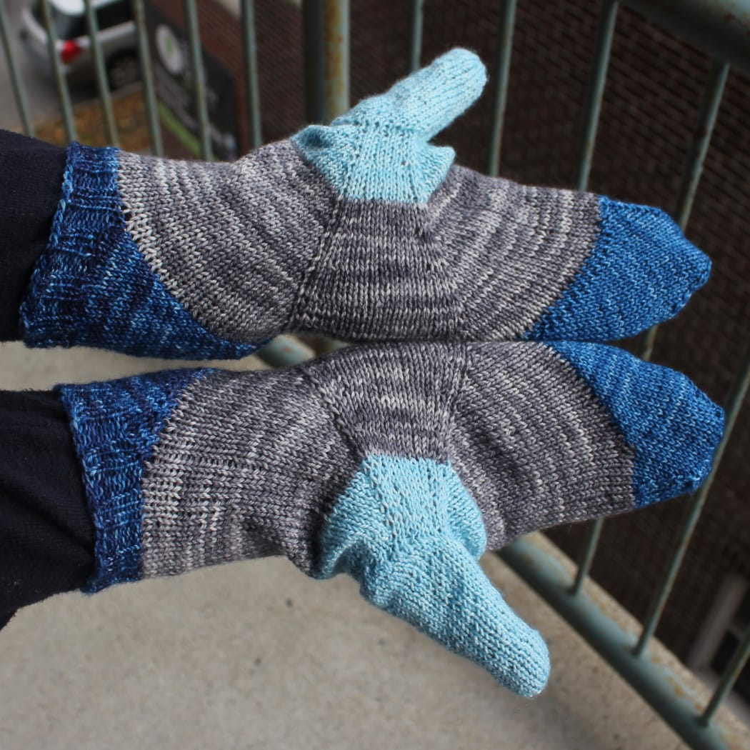Top-down view of palms of hands wearing mittens in shades of blue with a grey stripe across the palm between the blue sections.