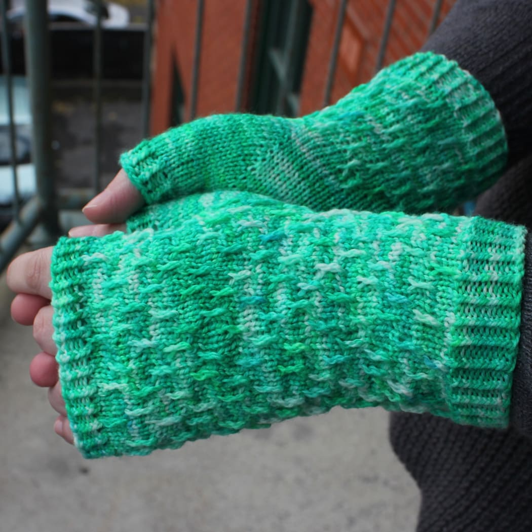 Side view of hands wearing bright green, white, and blue fingerless mitts with twisted surface detail.