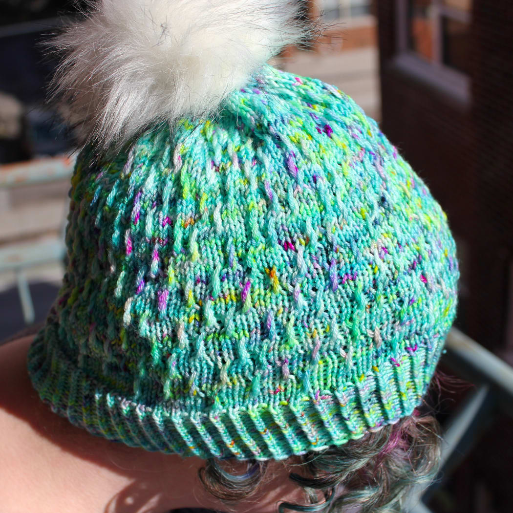 Close up of woman wearing bright green and rainbow hat with white pompom and twisted surface texture.