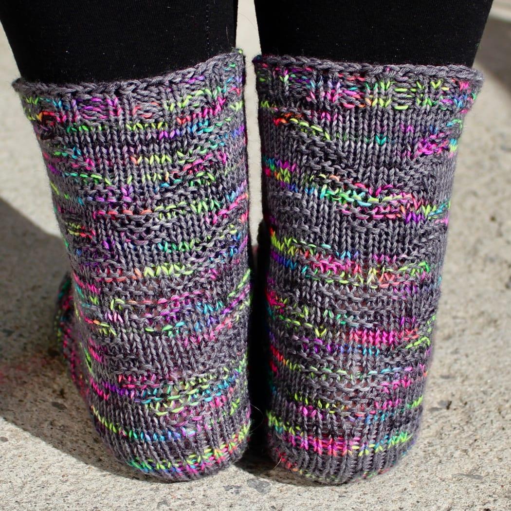 Back view of feet wearing dark grey and rainbow socks with raised chevron texture.