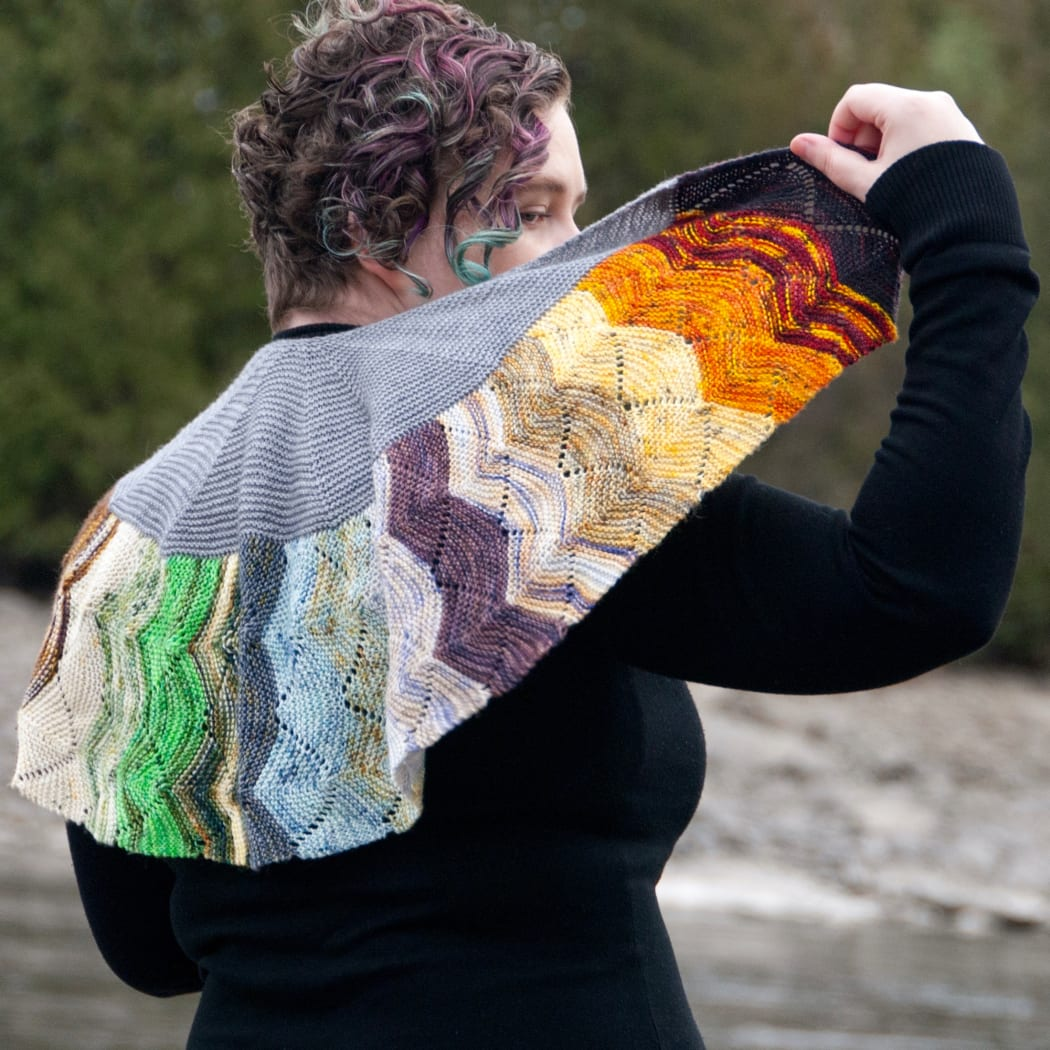 Woman wearing and holding a small, colourful crescent-shaped knitted shawl with undulating textured lines.