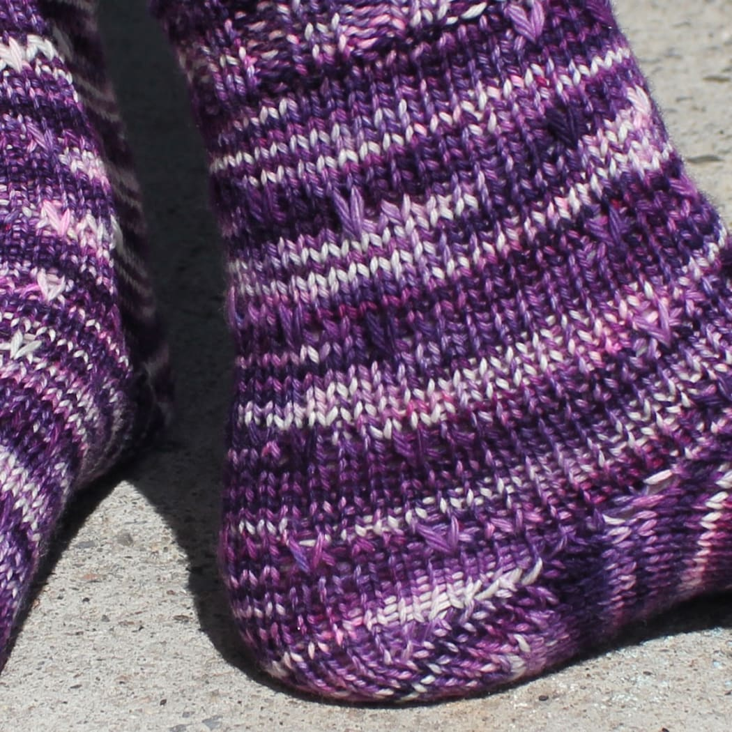 Close up of side and heel of dark purple, pink, and white socks with slipped-stitch texture.