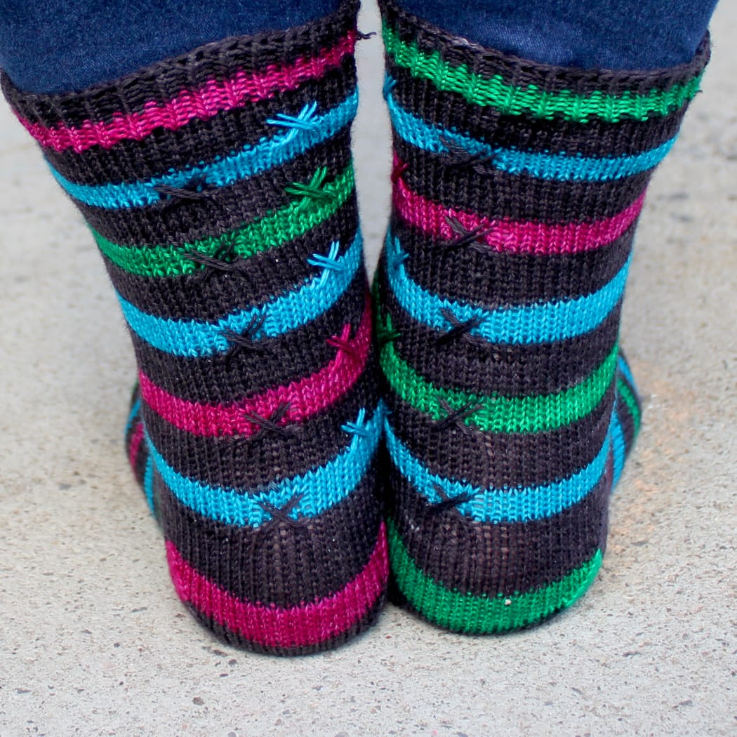 Back view of striped knitted socks with X stitch details on top of the stripes.