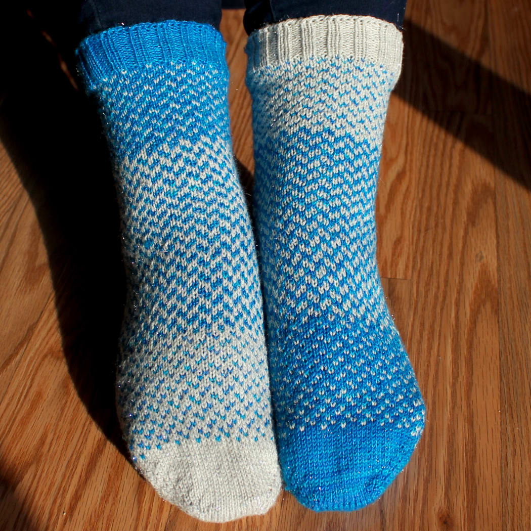 Front view of fraternal blue and white sparkly colourwork socks.