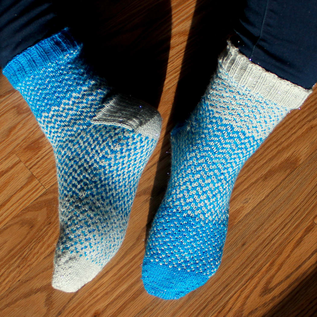 Blue and white sparkly colourwork socks shown on one foot from above and on the other from the side and sole.