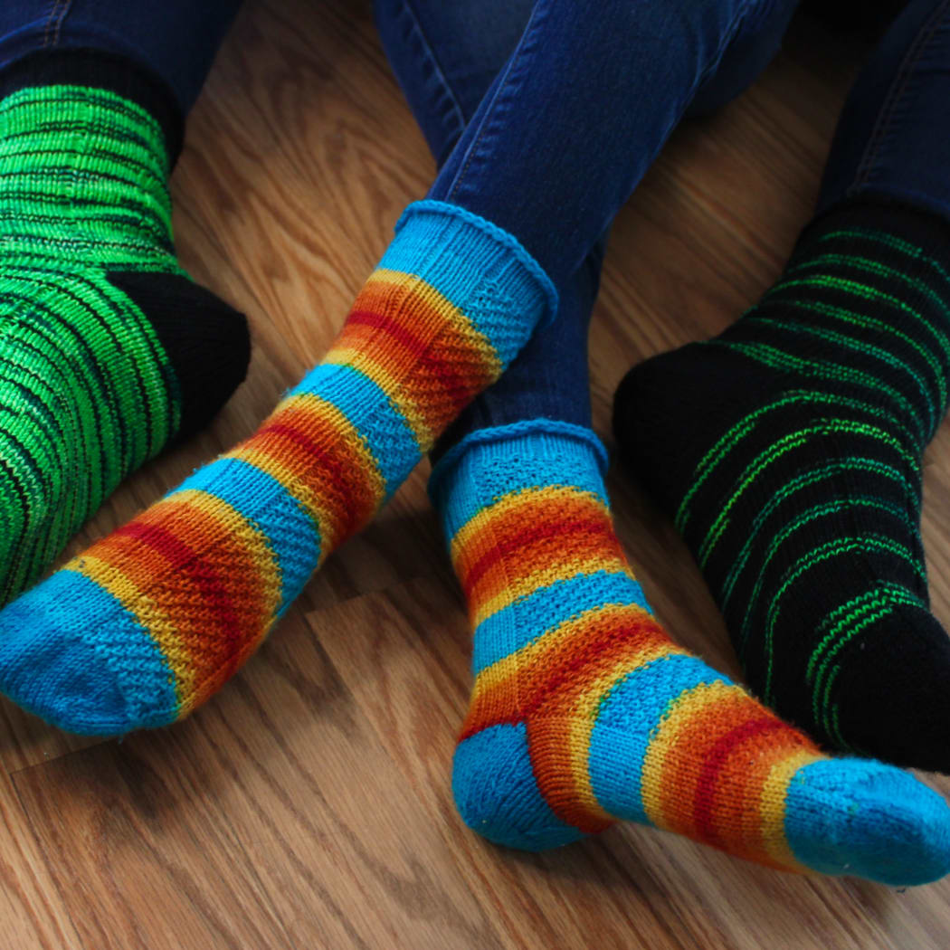 Crossed child feet wearing striped socks with texture detail and blue heels between adult feet wearing matching green and black socks with black heels.