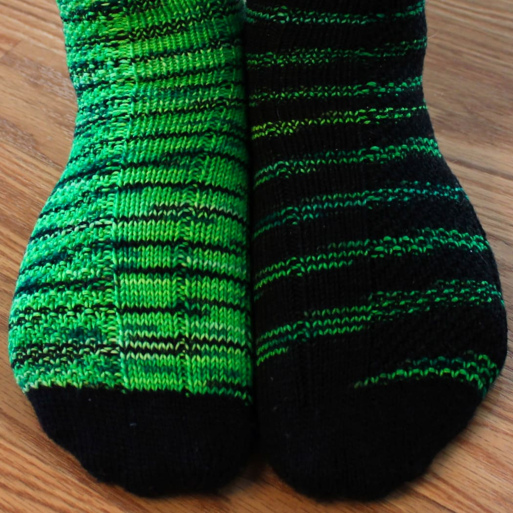 Close up of feet wearing green and black socks with texture detail.