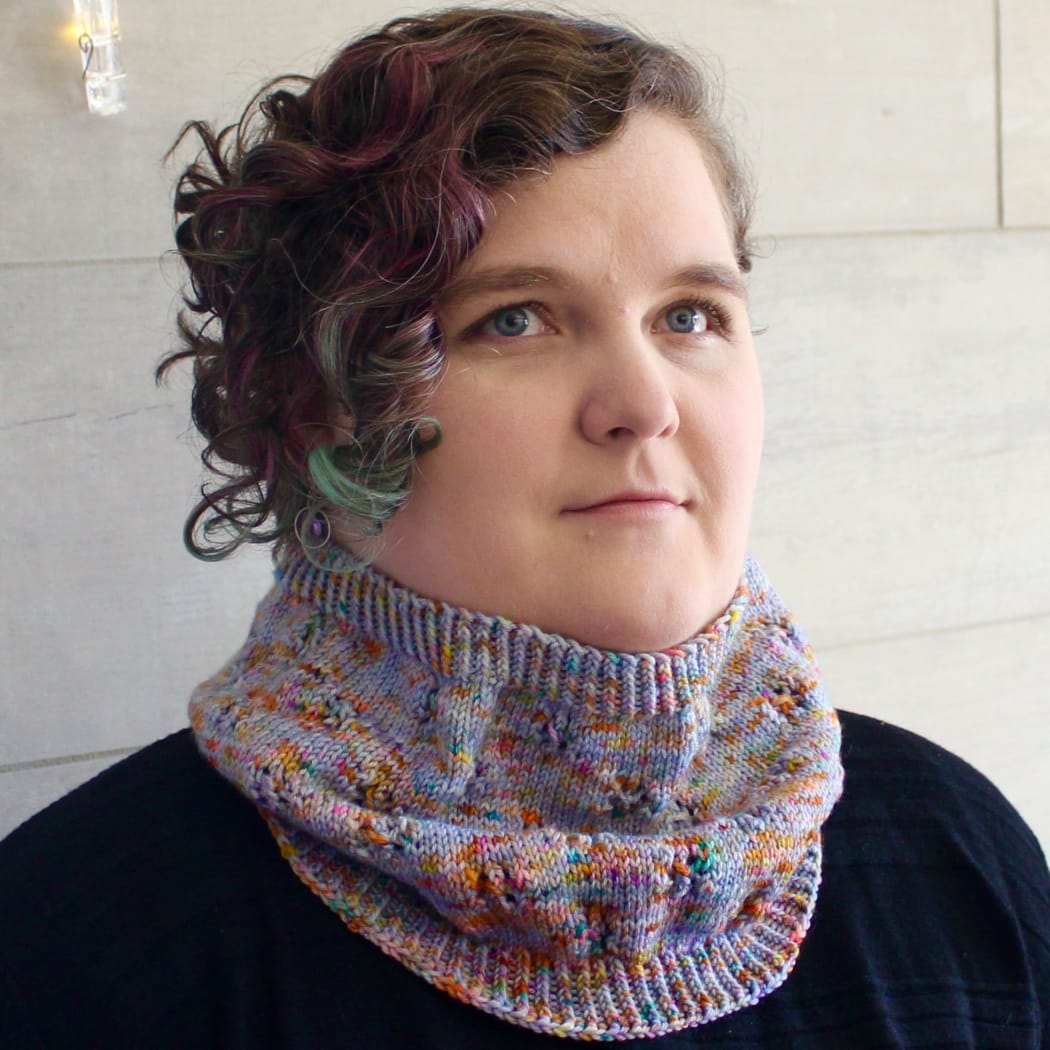 Woman wearing cowl that is light purple and rainbow-speckled knitted fabric with lace detail.