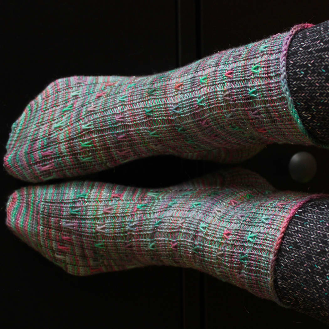 Feet wearing green ribbed socks with coral and purple spiralling surface detail.