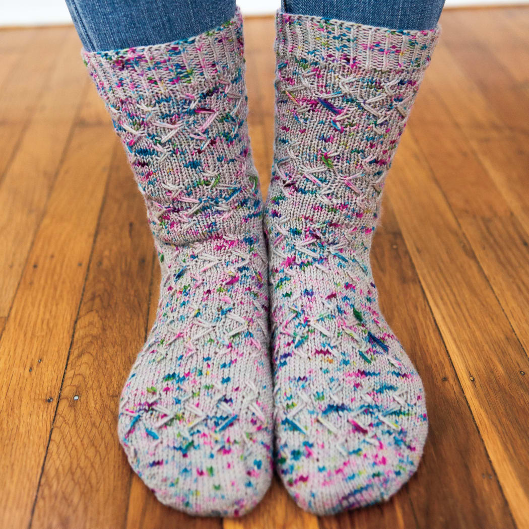 Front view of feet wearing grey knitted socks with blue and purple speckles and an angular slipped-stitch surface texture.