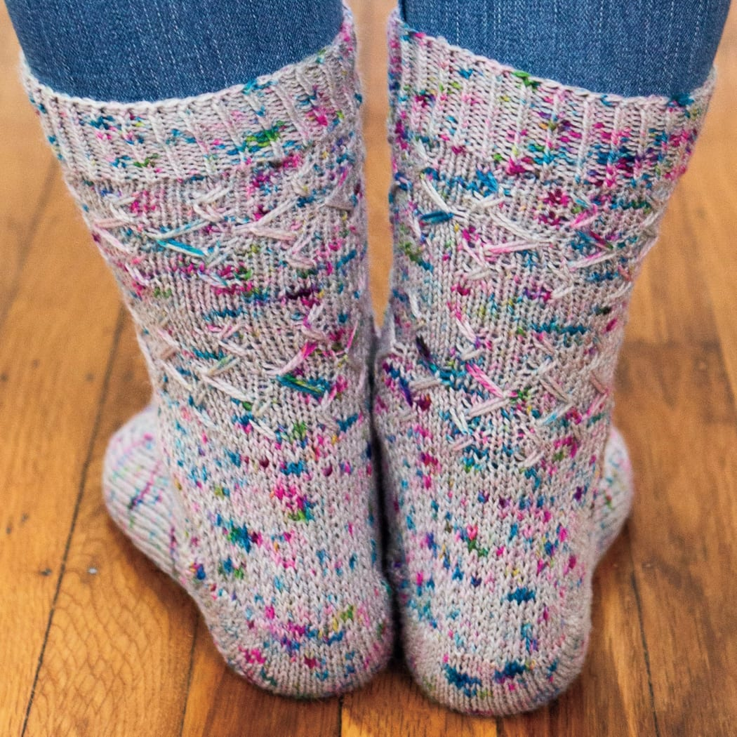 Back view of feet wearing grey knitted socks with blue and purple speckles and an angular slipped-stitch surface texture.