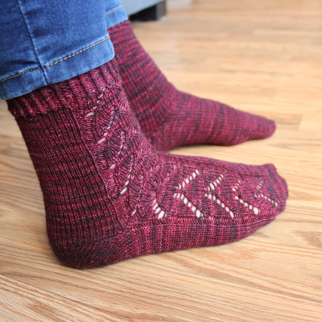 Side view of feet wearing red socks with lace panel of interlocking hearts.
