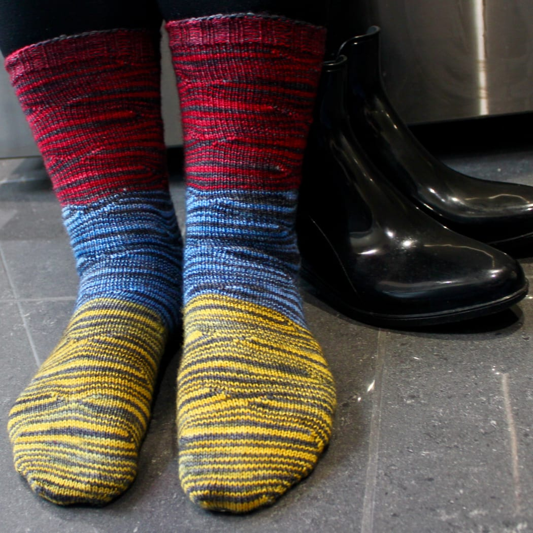 Front view of feet wearing red, yellow, and blue socks with distorted black stripes.