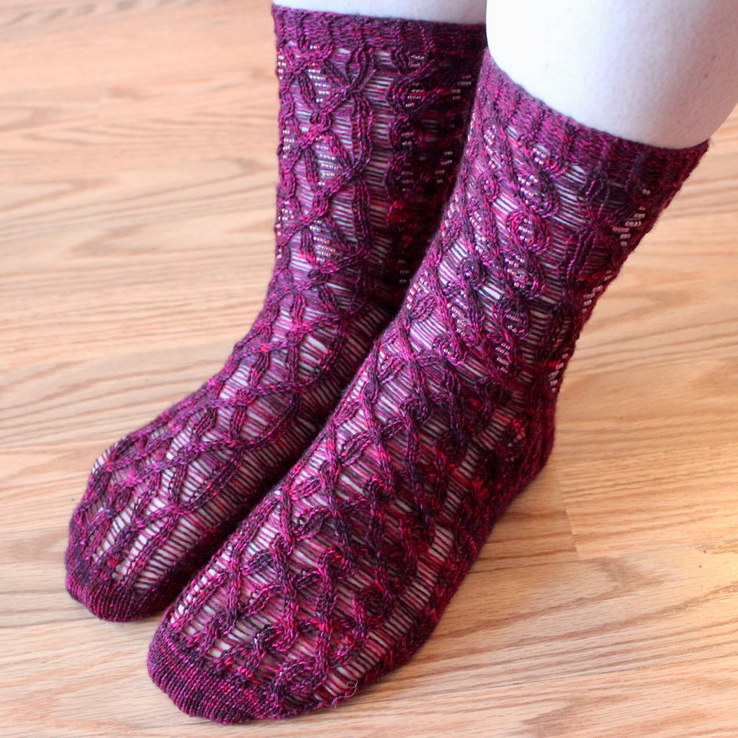 Feet wearing red cabled socks with beads on strands between the cable crosses.