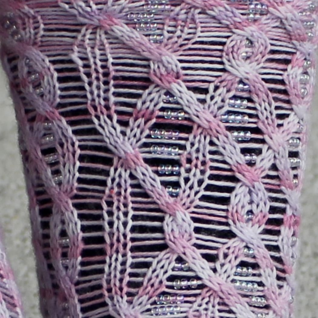 Close up of light pink cabled socks with beads on strands between the cable crosses.